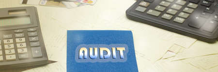 AUDIT text on a blue piece of paper on a writing desk, next to black calculators and a lot of checks