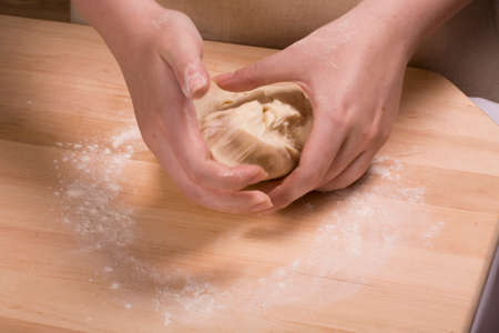 kneading: woman hands kneading  dough on wooden table