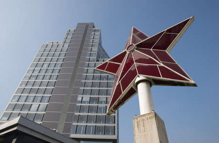 A red star monument is seen in front of a new office building. The red star is the symbol of socialism and communism. These political doctrines are adopted nowadays by China, North Korea and Cuba.