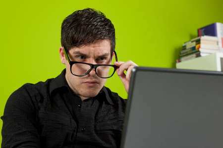 squinting: Young man squinting at the laptop