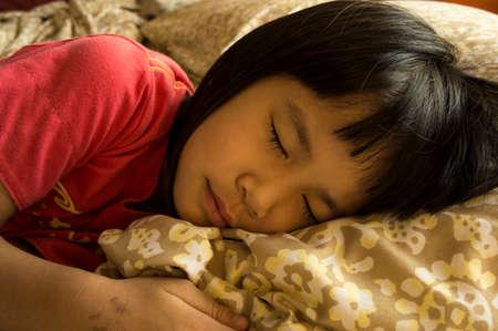 pyjama: little girl sleeping on warm bed Stock Photo