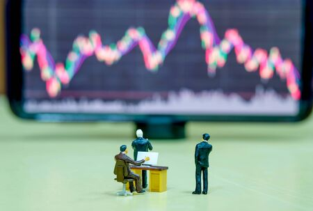 Miniature figure business people or Stock Trader looking at Blur Stock board for Graph Analysis