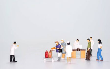 the miniature figure doll passenger wearing mask to protect Coronavirus or Covid-19 walking to Disease Control point that have Doctor and nurse isolate on White background