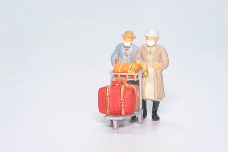 the miniature figure doll old lady passenger wearing face mask with travel suitcase and bag isolated on white background