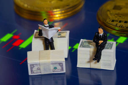 Miniature people businessman sitting on Dollar Banknote with market trading candlestick chart and Golden Coin in Background. Investing in Stock Market Trading concept 스톡 콘텐츠