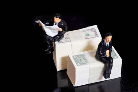 Miniature people businessman sitting on Dollar Banknote with Black Background. Investing in Stock Market Trading concept