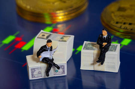 The Miniature people businessman sitting on Dollar Banknote with market trading candlestick chart and Golden Coin in Background. Investing in Stock Market Trading concept