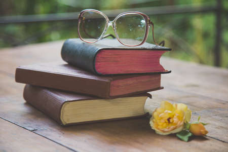 rose and the old book and spectacles on a table