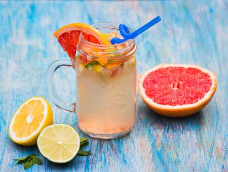 muddy: Grapefruit lemonade in pitcher of citrus around on natural wooden table on blue background