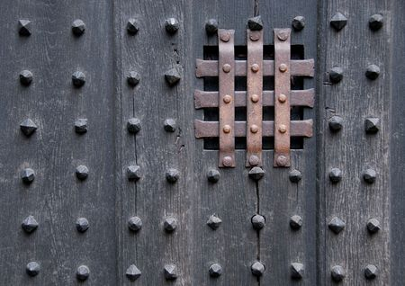 prison: Close-up shot of a dark, ancient, heavy, wooden door with metal spikes and bars over a tiny square window.