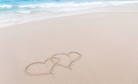 Two hearts drawn in the sand at the beach photo