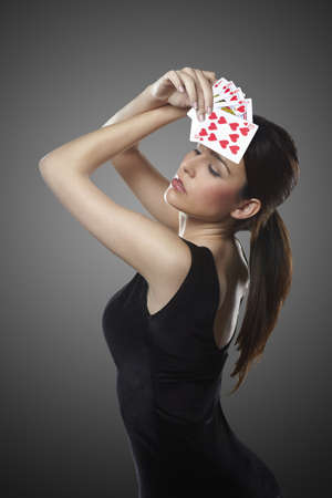 croupier: Sexy young woman with poker cards Stock Photo