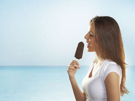 Woman holding a delicious ice cream on the sea