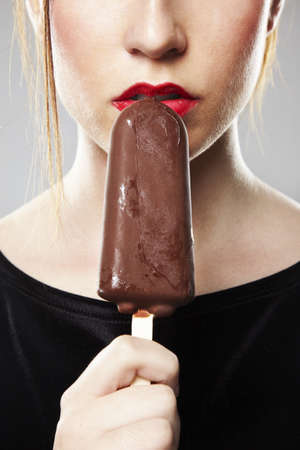 eating ice cream: Portrait of beautiful woman over grey background