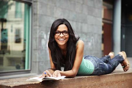 Chica guapa, sonriente y estudiar en un parque Foto de archivo - 16794216
