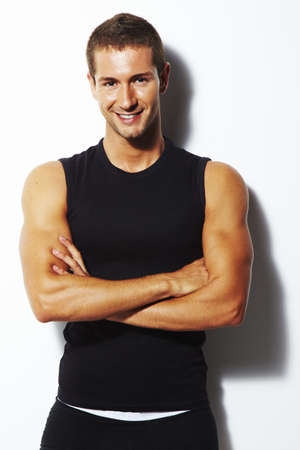 tank top: Strong and smiling man with crossed arms over white background