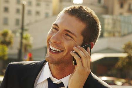 uomo felice: egli sta chiamando qualcuno per telefono cellulare per la strada Archivio Fotografico