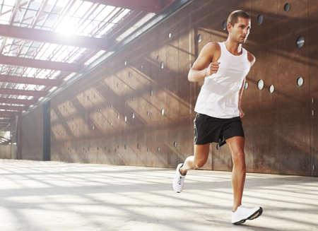 ropa deportiva: Atleta masculino caucásico haciendo ejercicio al aire libre