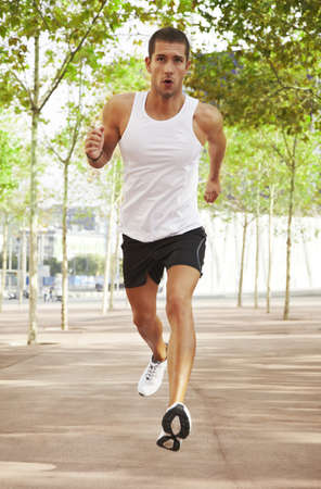caucasian male athletic jogging outdoor with green trees photo