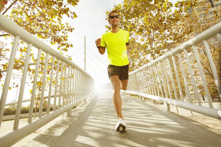man running with sunglasses on a background with trees
