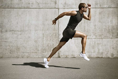 running shoes: young man jogging front cement wall Stock Photo