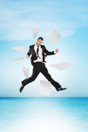 Success business man jumping with work papers on the sea photo