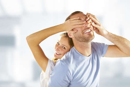 hand covering eye: Happy beautiful woman covering young man eyes