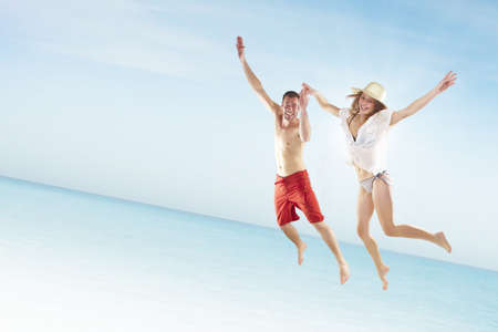 Beautiful young couple jumping on the beach photo