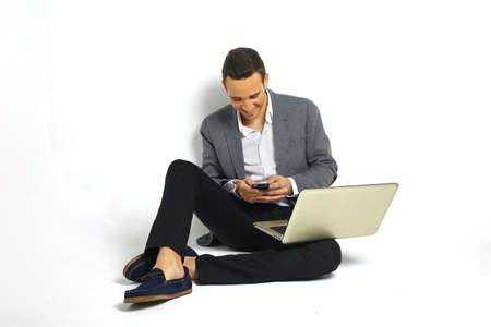 business man laptop: sonriente joven hombre de negocios con un ordenador port�til sentado en el piso de enviar sms con un smartphone