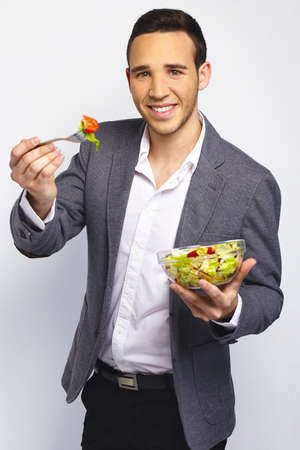 Young business man eating fresh salad photo