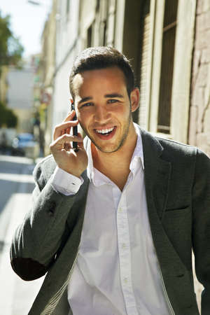 Businessman goes and calls on mobile in city street photo