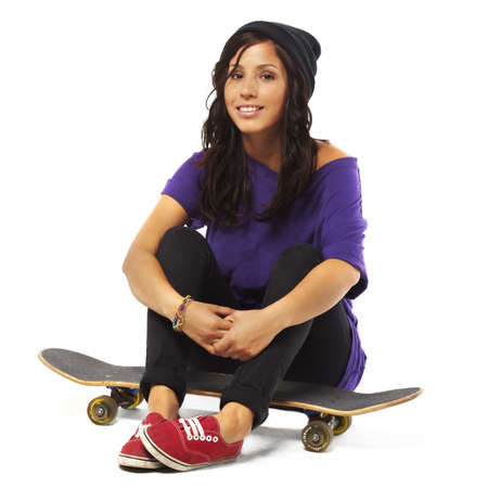 Young happy woman sitting on a skateboard photo