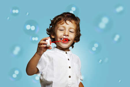 little caucasian boy with soap bubbles on blue background photo