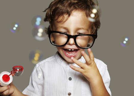 little caucasian boy with soap bubbles on grey background photo