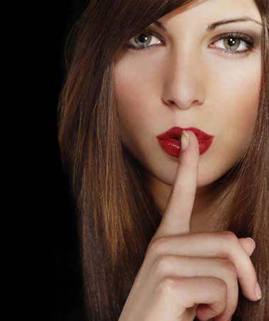 quiet adult: Ritratto di attraente giovane ragazza con un dito sulle labbra e marrone capelli lunghi