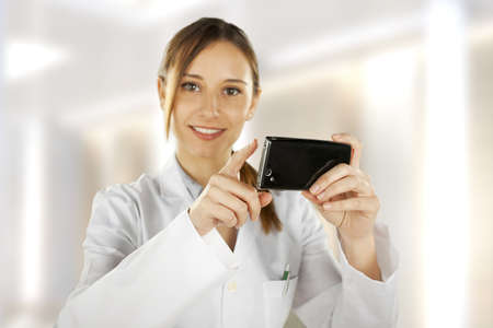 medical woman with mobile phone over white background photo