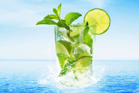 Glass of Mojito cocktail at the beach photo