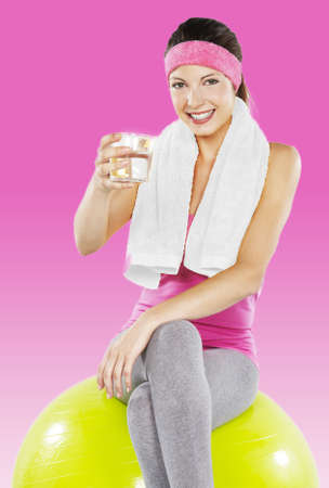 An isolated shot of a beautiful sporty caucasian woman holding a glass of water photo