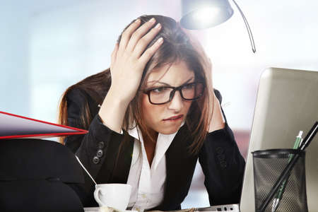 A young businesswoman is looking stressed as she works at her computer photo