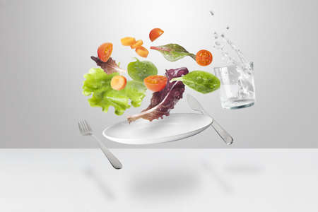 vegetables,fork, knife, glass of water and dish in suspension photo