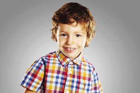 glücklich lachend kleinen Jungen auf grauem Hintergrund