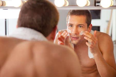 hombre afeitandose: Hombre joven que afeita en espejo del ba�o