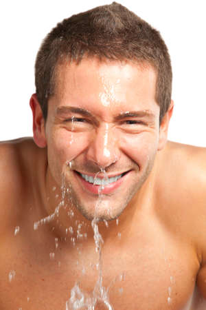 Young man splashing water on his face photo