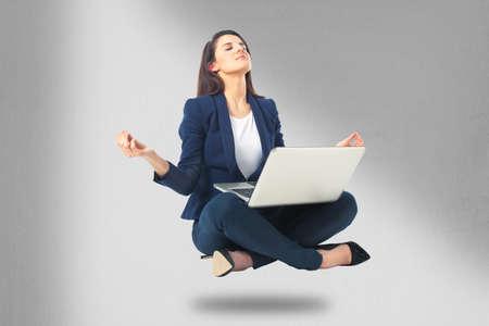 laptop stand: Beautiful business woman meditating and making yoga