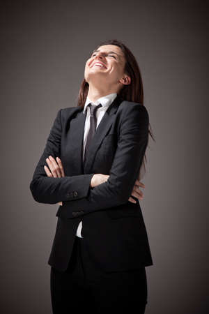 cross armed: Young businesswoman cross armed and smiling on a grey background Stock Photo