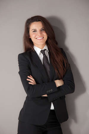cross ties: Young businesswoman cross armed and smiling on a grey background Stock Photo
