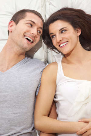A smiling couple lying with headphones photo