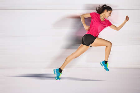 young woman jogging front cement wall