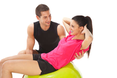 Young woman doing push ups on a fitness ball photo