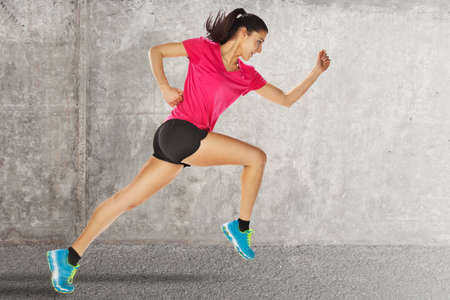 starting: young woman jogging front cement wall